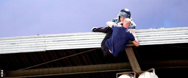 A man clings on to the stadium roof at a game between Arsenal Tula and Spartak Moscow