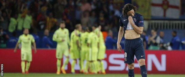 Edinson Cavani of PSG stands in front of celebrating Barcelona players