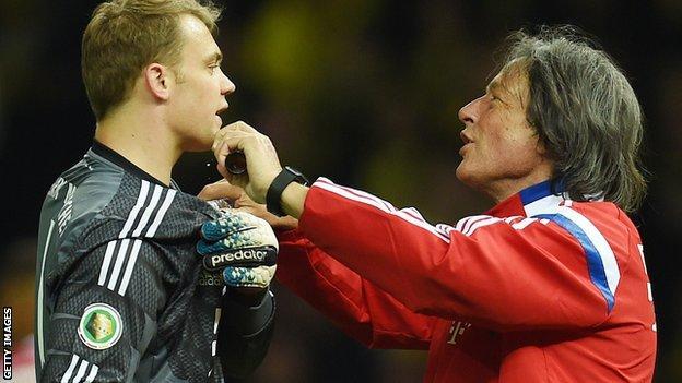 Hans-Wilhelm Mueller-Wohlfahrt treating goalkeeper Manuel Neuer