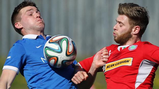 Linfield midfielder Stephen Lowry battles for the ball with Cliftonville opponent James Knowles at Solitude