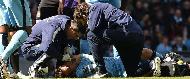 Man City's David Silva receives treatment before being taken off on a stretcher