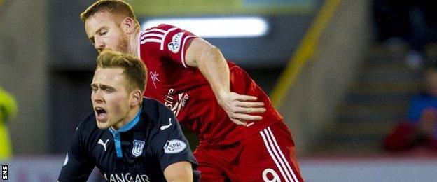 Dundee's Greg Stewart is challenged by Adam Rooney of Aberdeen