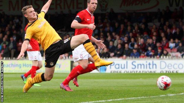Yan Klukowski of Newport County stretches out to challenge for a cross