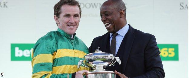AP McCoy is presented with the jockey's championship trophy by Ian Wright