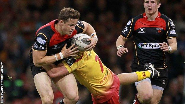 Dragons back Hallam Amos is tackled by Scarlets flanker James Davies during their 'Judgement Day' match at the Millennium Stadium