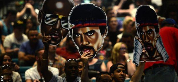 Fans hold up images of Mayweather and Pacquiao