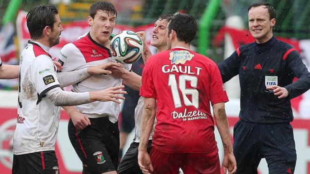 Glentoran and Portadown players are involved in heated exchanges during the big match at the Oval