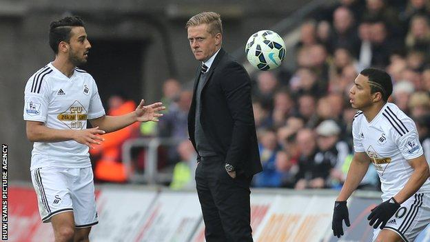 Swansea's manager Garry Monk looks on as Neil Taylor and Jefferson Montero restart from a throw-in against Stoke