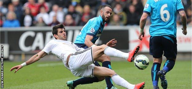 Swansea's Nelson Oliveira goes down under the challenge of Stoke's Marc Wilson, who was later sent off for two bookings
