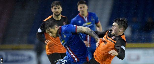 Greg Tansey attempts to hold off John Souttar, the United defender