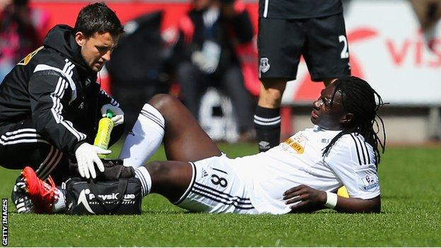 Bafetimbi Gomis (right) receives treatment