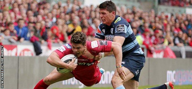 Scarlets wing Harry Robinson is pushed into touch just short of the line by Richard Smith of Cardiff Blues