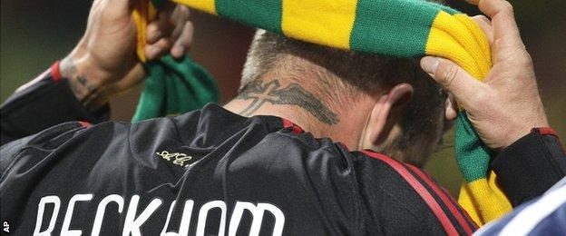 David Beckham puts on a green and gold scarf to show his support for Man Utd fans on his return to Old Trafford with Real Madrid in 2010