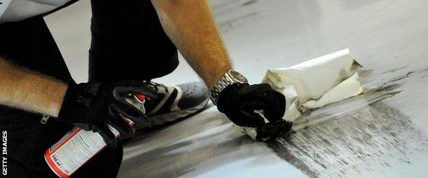 An engineer attempts to clean tyre marks from the garage
