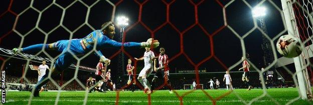 Brentford keeper David Button dives to try and keep out Fernando Amorebieta's late goal