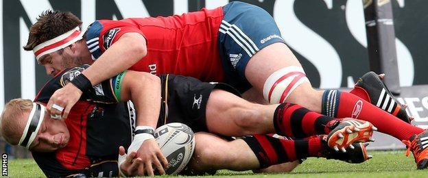 Munster's Billy Holland wrestles Dragons' Brok Harris to the ground in their Pro12 tie in Cork