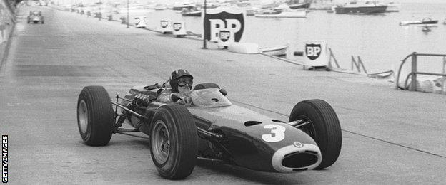 Graham Hill drives his BRM F1 car along the harbour straight at Monaco