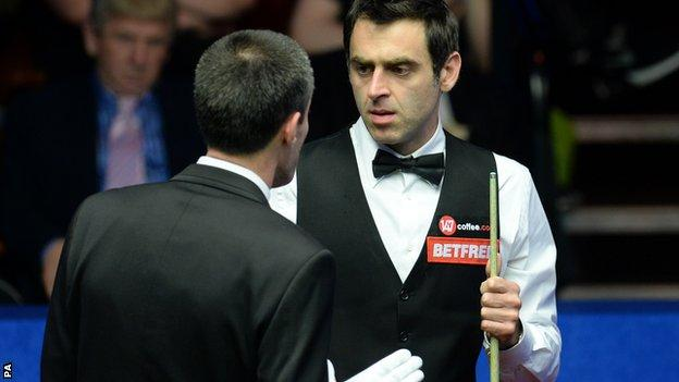 Ronnie O'Sullivan is spoken to by referee Olivier Marteel in his second round match against Matthew Stevens