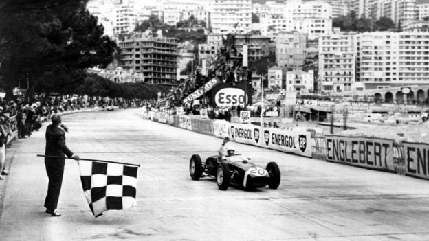 Stirling Moss of Britain raises his hand in victory after passing the finish line (and chequered flag) in first place at the Monaco Grand Prix Automobile race on May 14, 1961.