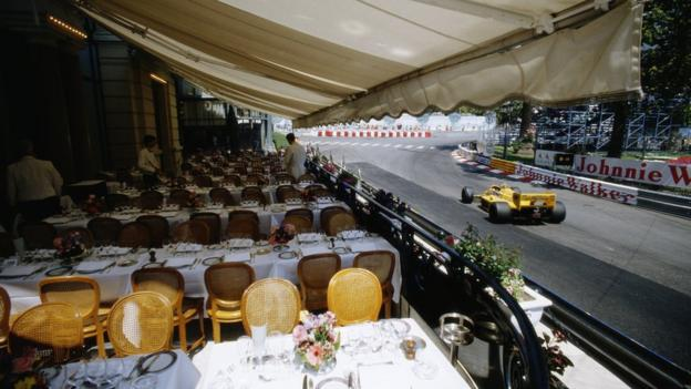 Ayrton Senna drives the 12 Camel Team Lotus Honda Lotus 99T past waiters and tables of a restaurant overlooking the circuit during practice for the Grand Prix of Monaco on 30 May 1987 on the streets of the Principality of Monaco in Monte Carlo