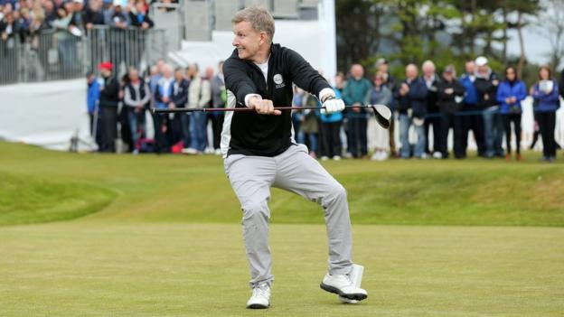 Comedian Patrick Kielty goes through a warm-up routine before taking his opening tee shot at Royal County Down