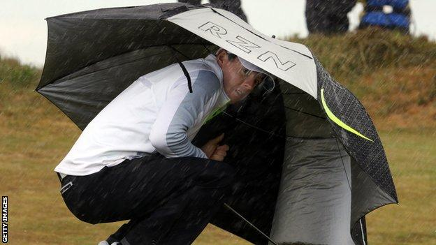 Rory McIlroy shelters from one of the many showers at Royal County Down