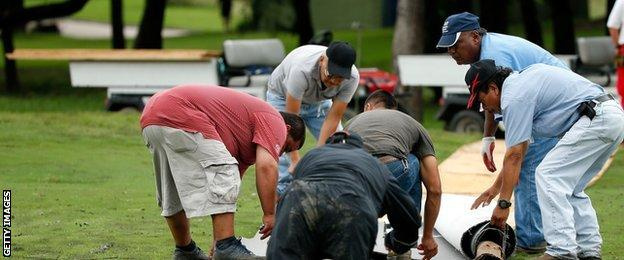 Workers at the Byron Nelson tournament put down a walkway on the 14th fairway