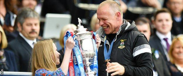 John Hughes is handed the Scottish Cup by his young daughter on the Hampden podium.