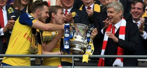 Aaron Ramsey (L) hands the FA Cup to Arsenal manager Arsene Wenger at Wembley