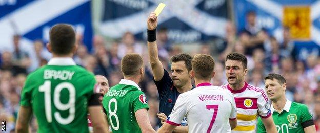 Republic of Ireland's James McCarthy is shown a yellow card by referee Nicola Rizzoli for an elbow into Russell Martin's face