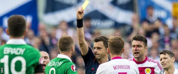 Italian referee Nicola Rizzoli shows James McCarthy a yellow card for elbowing Russell Martin in an aerial challenge