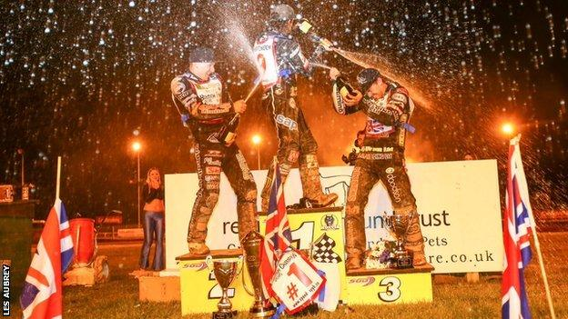British champion Tai Woffinden is sprayed on the rostrum at Monmore by Craig Cook and Danny King