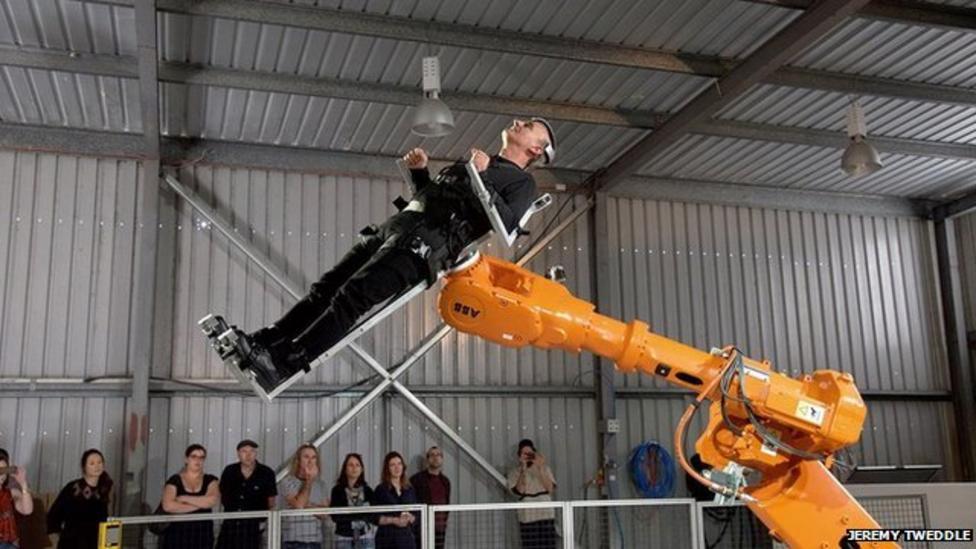 Man takes a ride on giant robot arm