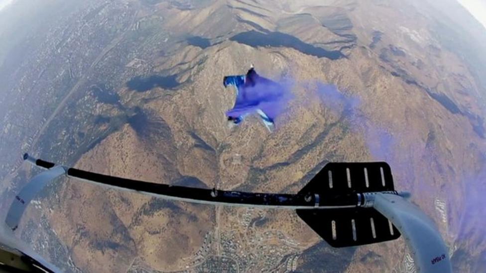 Wingsuit stuntman flies through flag