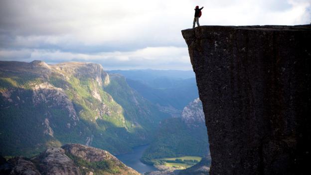 A hiker revels on top of Preikestolen in Norway (Credit: Credit: Anton Sokolov/iStock)