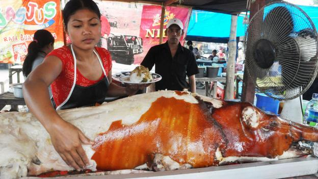 The roasted pig's golden brown skin chips off like paint (Credit: Credit: age fotostock/Alamy)