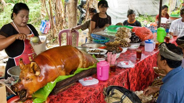 People feast on babi guling after it's been cooked for around two hours (Credit: Credit: age fotostock/Alamy)