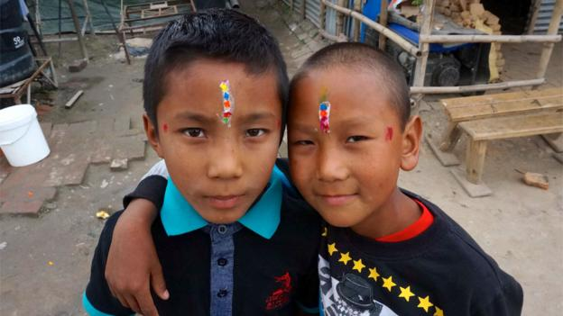 Grinning brothers, with multi-coloured tikas on their foreheads