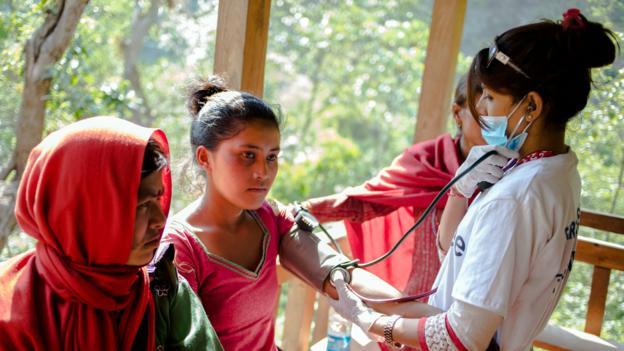A volunteer doctor treats an earthquake survivor at a makeshift clinic