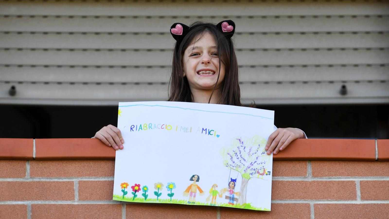 Girl holding up a colourful poster