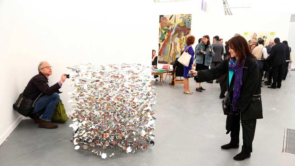 Frieze visitors are keen to photograph the multi-coloured mobile sculpture by Pae White, entitled Underthere, (2013). (Zuma/Rex Features)