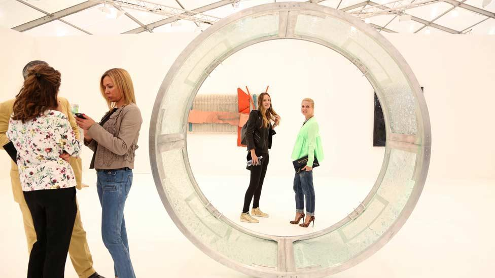 A giant metal doughnut or a piece of contemporary art?  Visitors at Frieze New York enjoy Dan Colen's large circular sculpture on the Gagosian stand. (Zuma/Rex Features)