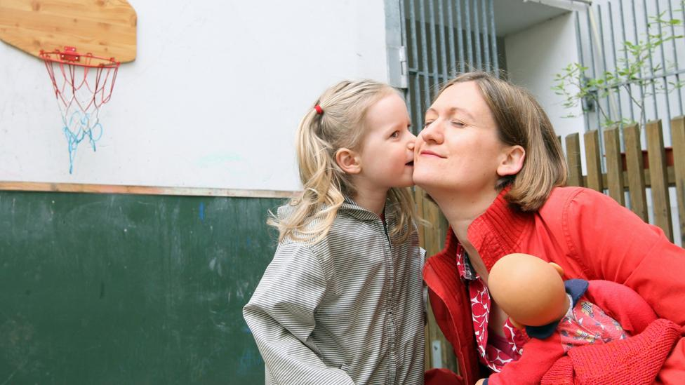 A three-year-old German girl kisses her mother goodbye. In some European countries, childcare is partly subsidized, making it easier for mothers to work. (Adam Berry/Getty Images)