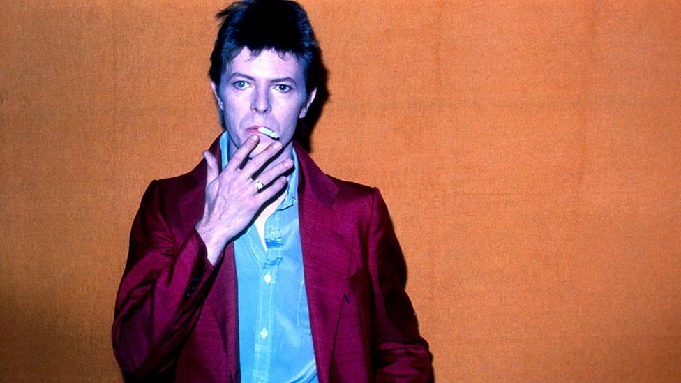 A 28-year-old Bowie is pictured at Hilversum TV studios in 1975, smoking meditatively and wearing a striking pink suit. (Rex Features)