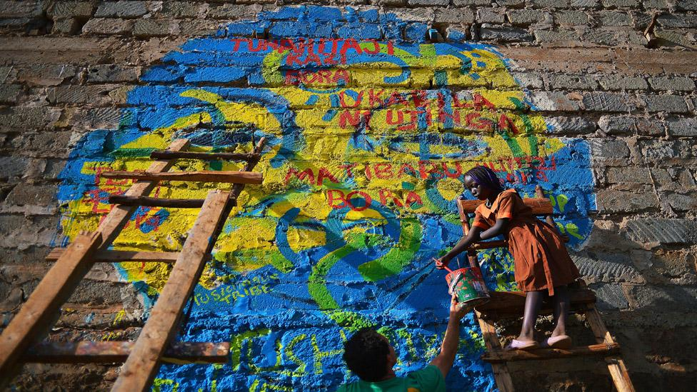 Children paint a mural at youth project 'Kibera Walls for Peace' (Carl de Souza /AFP/Getty Images)
