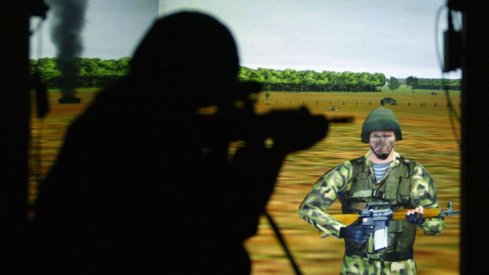 A British Army soldier takes aim at a video screen displaying a battlefield scenario. (Ian Waldie/Getty Images)