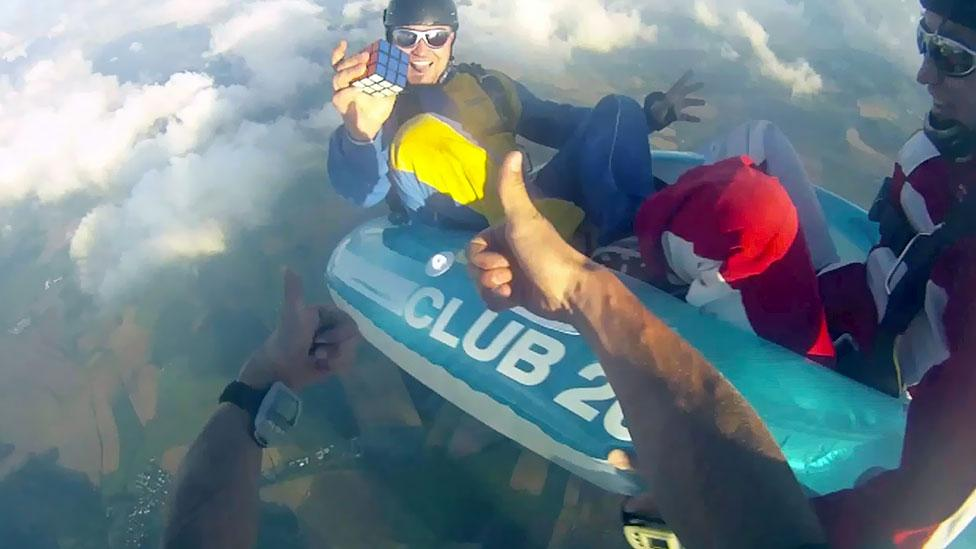 Cube enthusiasts try to solve it in unexpected places or manners – such as this person skydiving while working the puzzle. (Alamy)