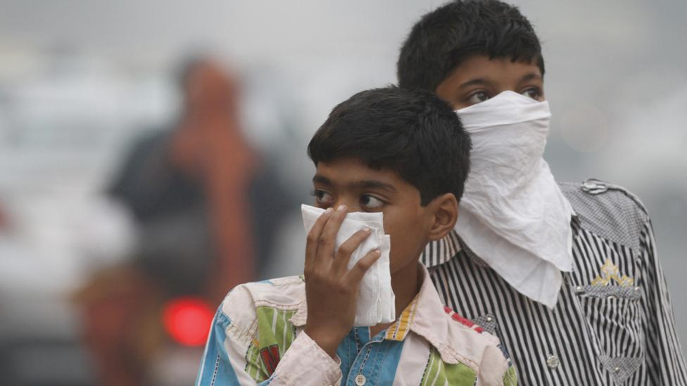 Children cover their mouths to avoid breathing in highly-polluted air in India's capital. (Sanjeev Verma/Hindustan Times/Getty Images)