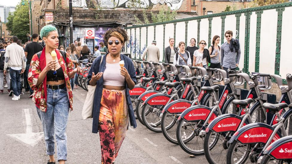 Women stroll in Shoreditch past the city's shared bicycles, a scheme that launched in 2010 (Credit: Nicola Ferrari/Alamy)