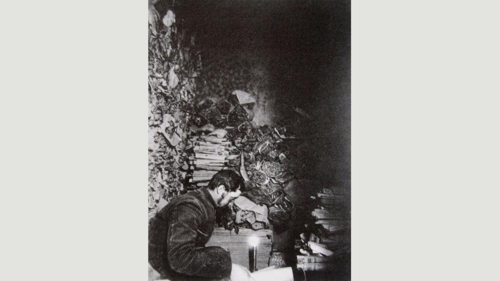 French sinologist Paul Pelliot in the Library Cave at Dunhuang in 1908 reading the manuscripts (Credit: The Musée Guimet)